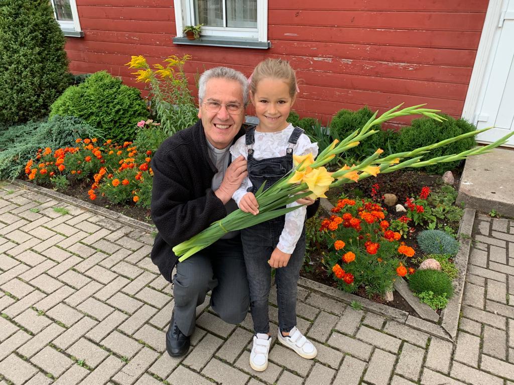 Don Rino con bimba al primo giorno di scuola a Telšiai
