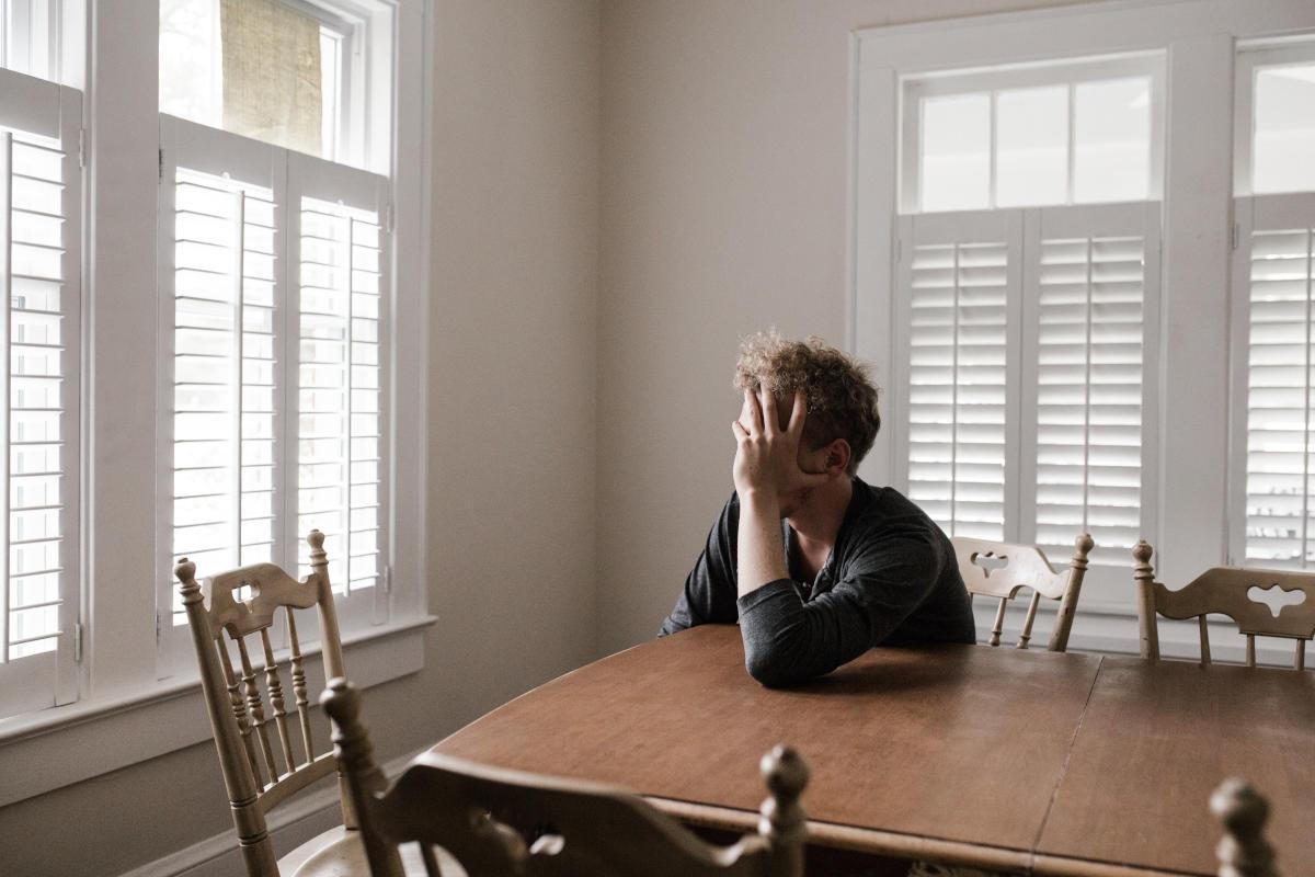 Uomo pensieroso seduto ad un tavolo