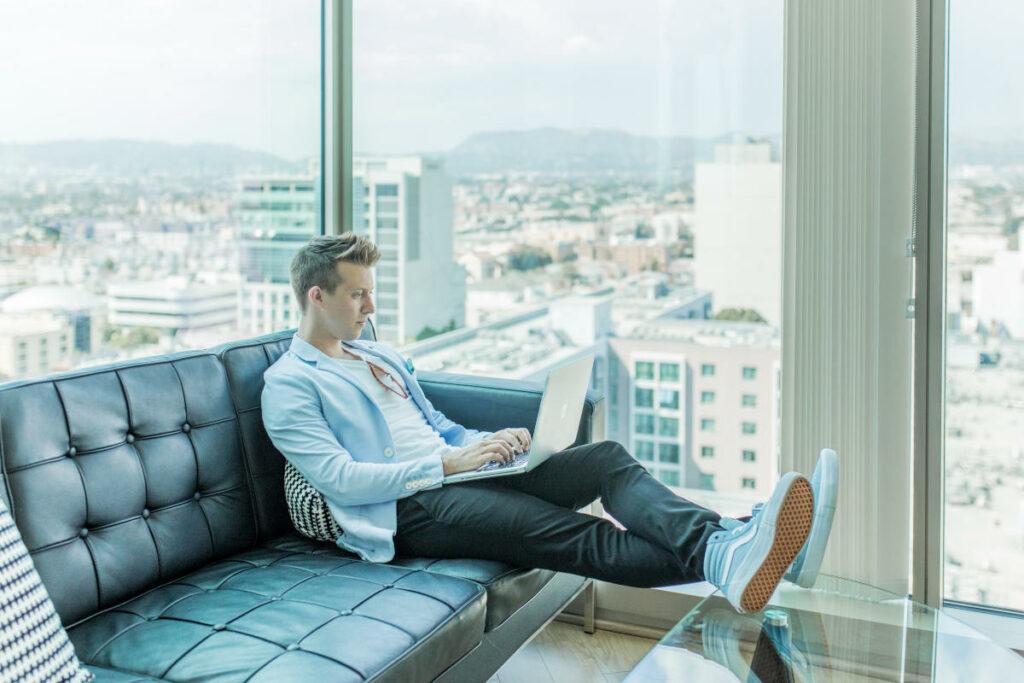 Uomo con notebook su divano