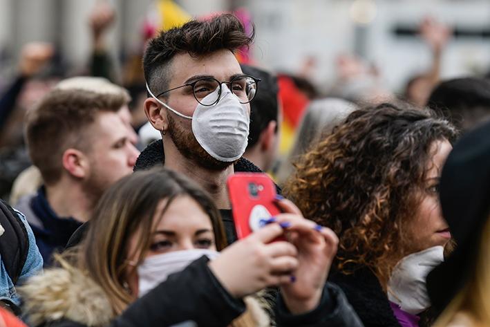 Giovani con smartphone e mascherina